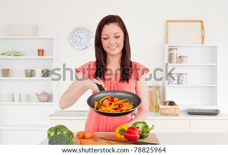 Pretty red-haired woman cooking vegetables in the kitchen in her apartment