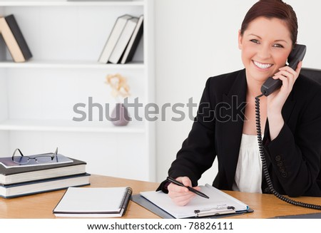 Pretty red-haired woman in suit writing on a notepad and phoning while sitting in an office