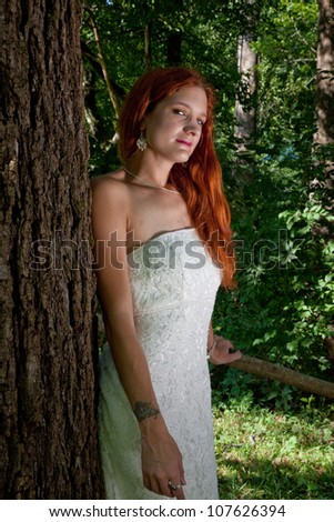 Pretty redhead bride in her wedding dress, standing outside by a tree and  looking at the camera with a thoughtful expression