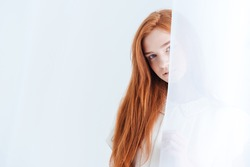 Pretty redhead woman peeking from curtain