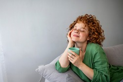 Pretty redhead woman savoring her mug of hot coffee as she sits on a sofa with eyes closed in contentment. Cup of tea or coffee. Woman drinking hot beverage and enjoying morning