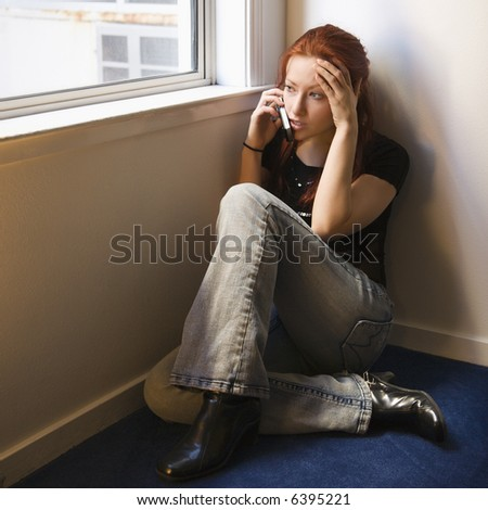 Pretty redhead young woman sitting on floor indoors by window talking on cellphone.