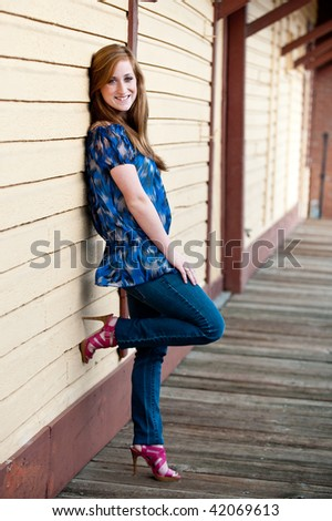 Pretty redheaded teen girl leaning against a wall
