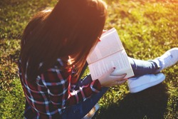 Pretty relaxed young woman reading a book at the lawn with sun shining