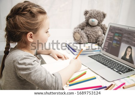 Pretty schoolgirl studying homework math during her online lesson at home, social distance during quarantine, self-isolation, online education concept