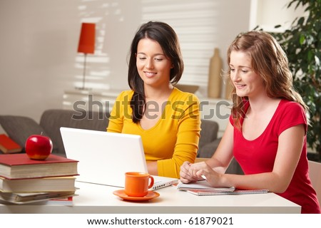 Pretty schoolgirls learning at home looking at laptop computer at table smiling.?