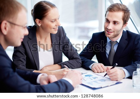 Pretty secretary looking at one of partners during paperwork at meeting - Shutterstock ID 128748086