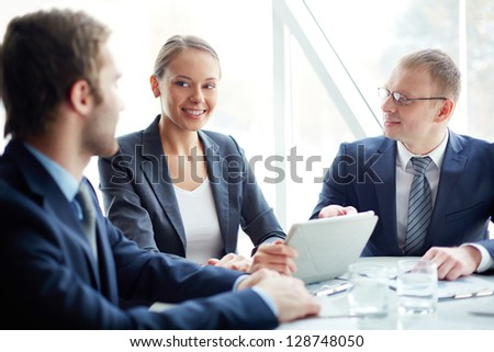 Pretty secretary looking at one of partners while planning work at meeting
