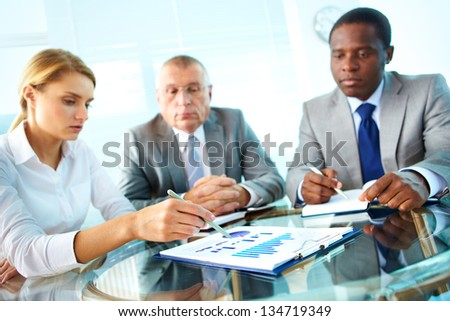 Pretty secretary pointing at paper while explaining something to her boss and colleague