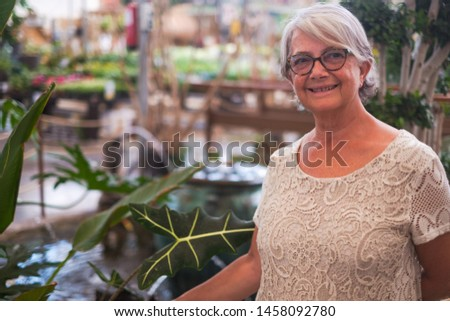 Pretty senior woman enjoying stay in the garden. Eyeglasses and white hair for one people