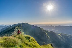 pretty senior woman resting during a hike in the early evening in warm dawn light on the ridge of the Nagelfluh chain in the Allgau Alps near Immenstadt, Bavaria, Germany