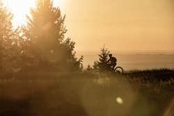 pretty senior woman riding her electric mountain bike in warm dawn sunlight heights of Salmas hight above Oberstaufen, with spectacular view on lake Alpsee,Allgau Alps, Bavaria Germany