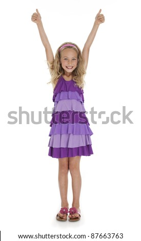 Pretty seven year old girl with arms extended overhead giving thumbs up gesture on white background.
