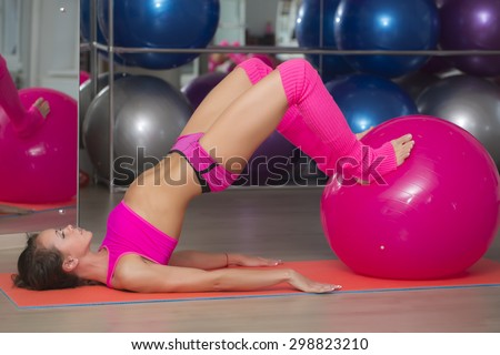 Pretty sexual straight sports woman with musculat body lying on mat on floor in erotic pose training with big pink ball in sport hall indoor, horizontal picture