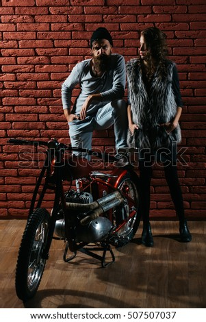 pretty sexy cute woman or girl with young handsome bearded man hipster or biker with long beard near metallized motorbike or motor cycle with wheels on red brick wall background in garage #507507037