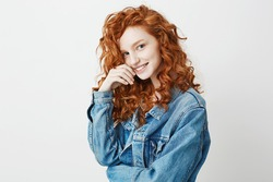 Pretty shy ginger girl smiling looking at camera over white background. Copy space.