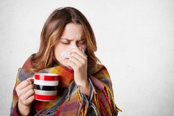 Pretty sick woman has runnning nose, rubs nose with handkerchief, drinks hot beverage, wrapped in warm blanket, has high temperature and cold, isolated over white background. Sneezing female
