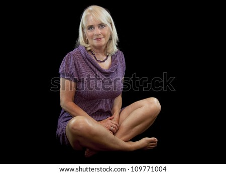 Pretty sixty year old woman posing in a lavender dress.