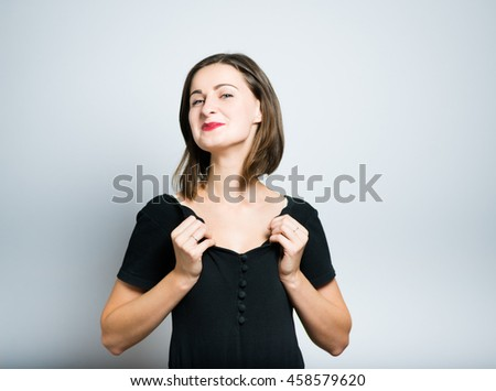 Pretty slim girl proud of herself, studio photo isolated on a gray backgroundd