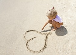 Pretty small girl drawing a heart shape on sand