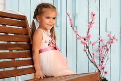 Pretty small girl in beautiful dress sits on the wooden bench and looks dreamy, beauty and fashion concept, indoor portrait