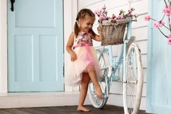 Pretty small girl in beautiful dress stay near the vintage white bicycle with basket with flowers over white wooden wall, beauty and fashion concept, outdoor portrait