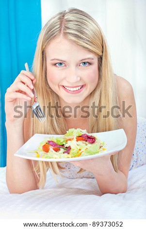 Pretty smiled woman eating salad in bed
