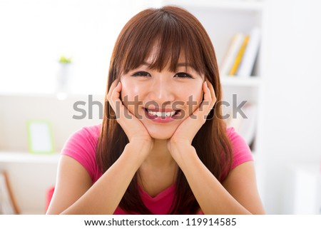 Pretty smiling Asian girl holding her face sitting at home