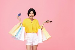 Pretty smiling Asian woman with shopping bags showing credit card in hand studio shot isolated on pink background