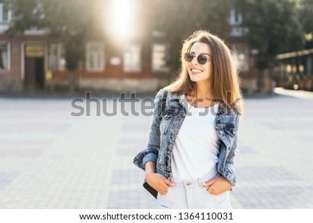 Pretty smiling brunette girl walking on the street #1364110031