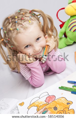 pretty smiling caucasian blond girl with adorable natural smile and holding bathc of pencils in hand lying on floor