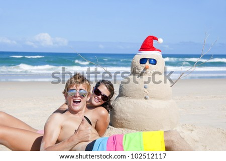 Pretty smiling couple having fun at Australian beach with snowman made out of sand wearing sunglasses at christmas eve.