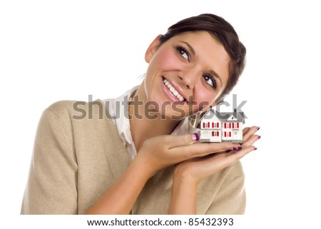 Pretty Smiling Ethnic Female Daydreaming with Small House Isolated on a White Background.