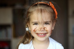 Pretty smiling girl dirty with chocolate, food and drink concept, chocolate face, indoor emotional portrait