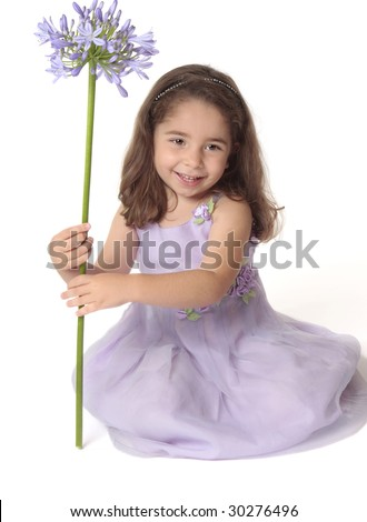 Pretty smiling girl holding a purple flower.