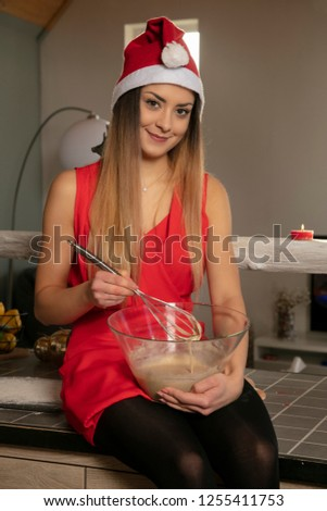 pretty smiling girl in Christmas clothing sitting on the table and preparing cake for baked goods