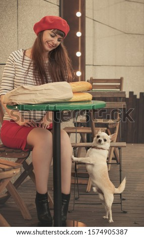 Pretty smiling girl in red beret, skirt and striped jacket sits at the green table in cafe with french bread baguette in paper bag. Her chihuahua dog poses near. French style picture.