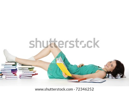 Pretty smiling girl lying on floor resting feet and head on colorful book stacks reading, isolated on white background with plenty of copy-space.