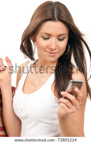 Pretty smiling girl reading texting a message on the cellphone mobile and holding shopping bags in hands on a white background