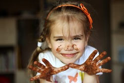 Pretty smiling girl showing her arms dirty with chocolate, food and drink concept, chocolate face, indoor emotional portrait