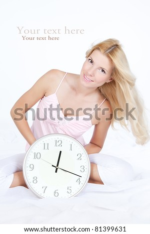 Pretty smiling girl sitting on the bed with clock
