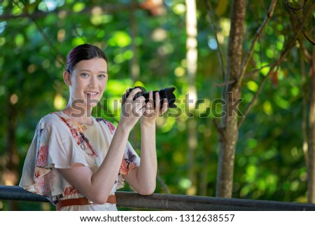Pretty smiling girl taking photos in a sunlit garden with her digital camera