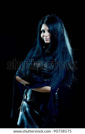 Pretty smiling gothic girl with long black hair on black