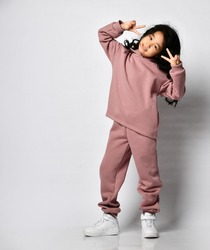 Pretty smiling little curly-haired Asian girl in warm pink jumpsuit standing and showing her face with her fingers against her eyes against the background of a white wall. Trendy kids fashion, stylish