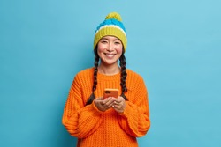 Pretty smiling millennial girl with two pigtails dressed in knitted hat sweater uses mobile phone for surfing social networks uses wireless internet isolated over blue background. Technology concept