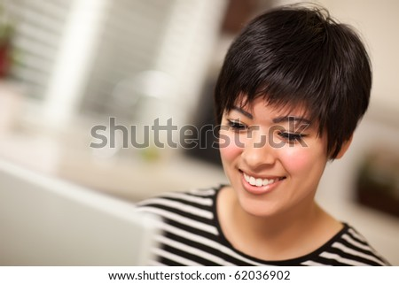 Pretty Smiling Multiethnic Woman Using Her Laptop Computer.