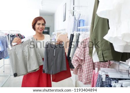 Pretty smiling pretty Vietnamese woman choosing pair of shorts