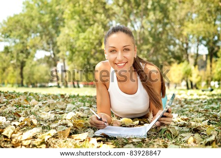 pretty smiling student girl in park with book