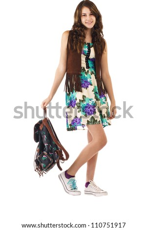 Pretty smiling teenage girl in flowered dress and fringed vest strolls carrying a backpack. Vertical, isolated on white, copy space.