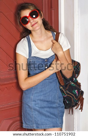 Pretty smiling teenage girl in sunglasses and fashionable back to school denim dress. She carries a backpack and leans against old red door. Vertical, copy space.